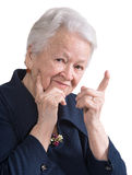 Smiling old woman pointing upwards Stock Image