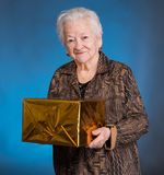 Smiling old woman with present box Stock Images