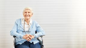 Smiling old woman sits in wheelchair in retirement home. Smiling old woman or grandmother sits in wheelchair in retirement home royalty free stock photography