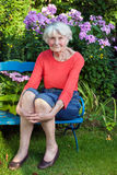 Smiling Old Woman Sitting on the Garden Bench. Close up Portrait of Smiling Old Woman Sitting on the Wooden Bench at the Garden While Looking at the Camera Stock Image