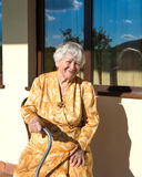 Smiling old woman sitting near the house Royalty Free Stock Image