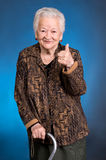 Smiling old woman standing with a cane Royalty Free Stock Image