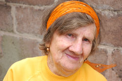 Smiling old woman in yellow blouse and headscarf Stock Photo