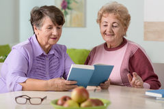 Smiling old women reading Stock Photos