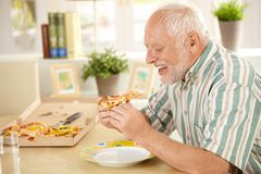 Smiling older man eating pizza slice Royalty Free Stock Image