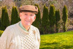 Smiling Older Man. Smiling senior male wearing fishermans sweater and wool cap outside. Trees and lawn in background. Sunny. Copy space stock photo