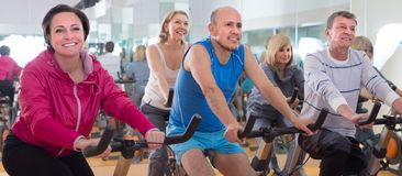 Older people do sports on exercise bikes. Smiling older people do sports on exercise bikes. focus on male in the centre royalty free stock images