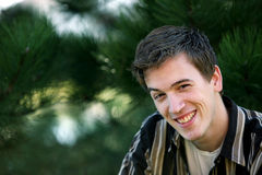 Smiling older teen boy. Handsome teen boy sitting outside Stock Photo
