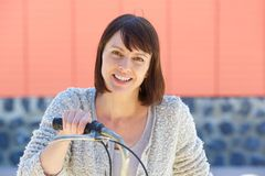 Smiling older woman with bike. Close up portrait of a smiling older woman with bike Stock Photo