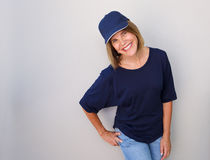 Smiling older woman with cap against gray wall Stock Images