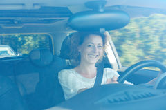 Smiling older woman in car on commute. Portrait of smiling older woman in car on commute Royalty Free Stock Images