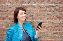 Smiling older woman reading text on cell phone Royalty Free Stock Image
