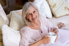 Smiling older woman sitting on couch drinking coffee Royalty Free Stock Photos