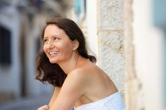 Smiling older woman sitting outside Stock Photo