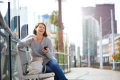 Smiling older woman sitting outside with mobile phone Stock Photography