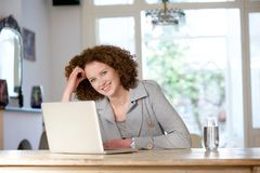 Smiling older woman sitting at table using laptop Stock Photos