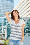 Smiling older woman standing in city with hand in hair royalty free stock photography