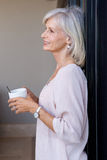 Smiling older woman standing in home drinking coffee. Close up portrait of smiling older woman standing in home drinking coffee Royalty Free Stock Photos