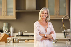 Smiling older woman standing in modern kitchen Royalty Free Stock Images