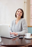 Smiling older woman using laptop at home Royalty Free Stock Photography