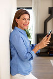 Smiling older woman using mobile phone and home Royalty Free Stock Images