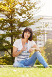 Smiling older woman with water bottle sitting in grass Stock Photos