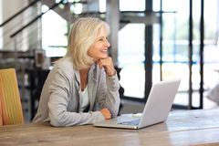 Smiling older woman working laptop computer indoors Royalty Free Stock Photography