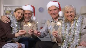 Smiling oldsters in New Year costumes holding sparklers, Christmas celebration. Stock footage stock footage