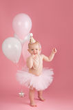 Smiling One Year Old Birthday Girl Wearing a Pink Tutu. A portrait of a smiling one year old baby girl wearing a pink tutu, string of pearls and birthday hat Royalty Free Stock Images