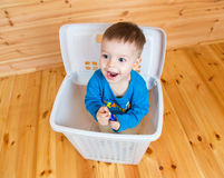 Smiling one year old boy getting out from garbage can. On  wooden background Royalty Free Stock Images