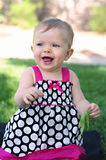 Smiling One Year Old Girl Outdoors. A smiling one year old girl baby with blue eyes holding some leaves Stock Photo