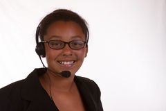 Smiling operator. Head and shoulders of a young African American business woman wearing headset over white stock image