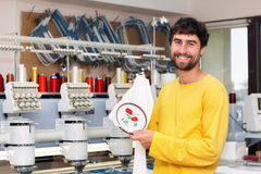 Smiling operator of automatic embroidery machines. Happy smiling operator of automatic embroidery machines working at his workplace royalty free stock photo
