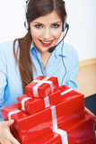 Smiling operator seat at table with red gift box. Happy busines Royalty Free Stock Photos
