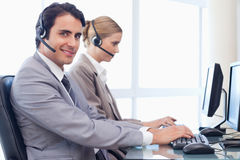 Smiling operators using a computer Royalty Free Stock Photo