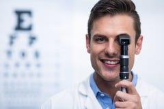 Smiling optometrist looking through ophthalmoscope. Close-up of smiling optometrist looking through ophthalmoscope in ophthalmology clinic Stock Image
