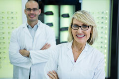 Smiling optometrists standing with arms crossed. Portrait of smiling optometrists standing with arms crossed in optical store Stock Photos