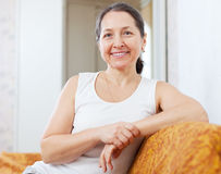 Smiling ordinary mature woman. In home interior Royalty Free Stock Image