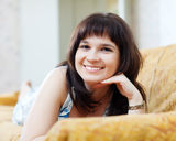 Smiling ordinary woman lying on couch. At home Royalty Free Stock Photography