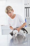 Smiling owner holding his cat. In medical office royalty free stock photos