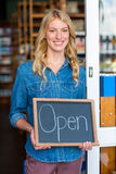Smiling owner holding open signboard in supermarket Royalty Free Stock Photo