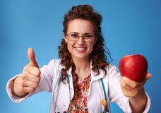 Paediatrician doctor giving an apple and showing thumbs up Royalty Free Stock Photo