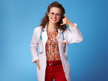 Smiling paediatrician doctor showing call me gesture on blue Royalty Free Stock Photography