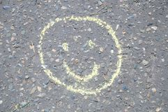 Smiling painted face with colorful chalks on asphalt, smiley sign sketched outdoor by children while walking. In the park royalty free stock photography