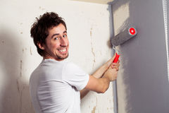 Smiling painter. Smiling young man painting the wall with roll Stock Photos