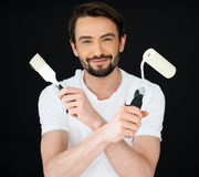 Smiling painter holding a roller and brush Stock Photography