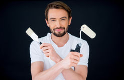 Smiling painter holding a roller and brush stock image