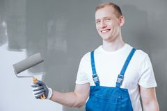 Smiling painter with paint roller. Smiling painter in blue overalls standing against grey wall and holding a paint roller stock images