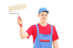 Smiling painter in a uniform holding a roller Royalty Free Stock Images