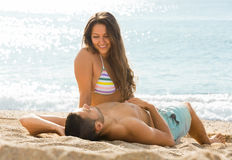 Smiling pair laying on sand beach Stock Photography
